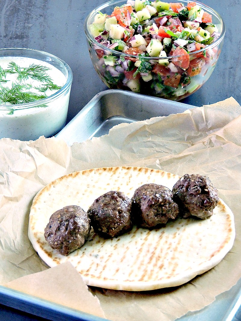 Gyro meatballs on a pita round on a parchment paper lined baking sheet with tzatziki and cucumber relish in bowls.