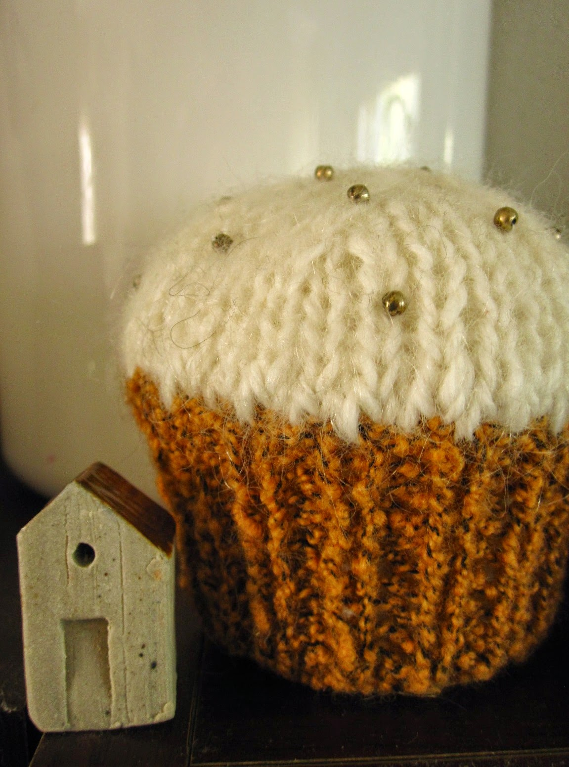 A small clay house displayed next to a full-sized knitted cupcake.