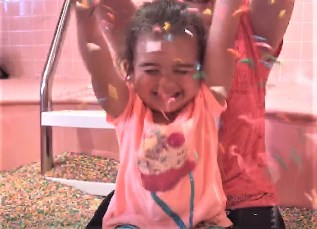 A toddler plays in colorful sprinkles