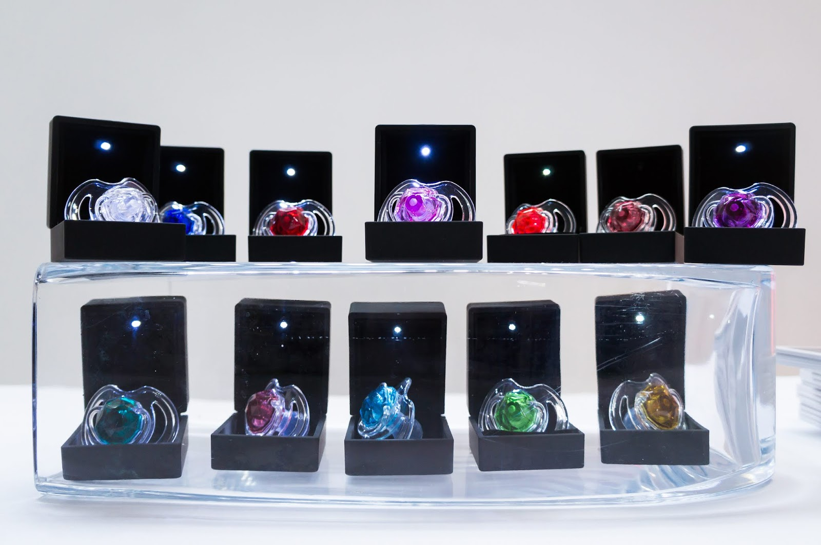 twelve colourful dummies pacifiers on display in black jewellery boxes at nuby big reveal event