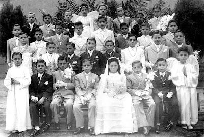 """Año 1948: Niños de un Colegio de hijos de obreros ferroviarios, de padres mayoritariamente """"rojos"""" exiliados en Lérida, el día de su Primea Comunión. Se les ve """"torturados"""" por la """"dictadura franquista"""", mal vestidos y famélicos (soy el 4º sentado empezando por la izquierda con cara de """"mala uva"""", al lado de la niña)"""