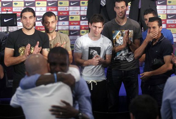 Barcelona player Éric Abidal embraces a technical staff as his teammates applaud him