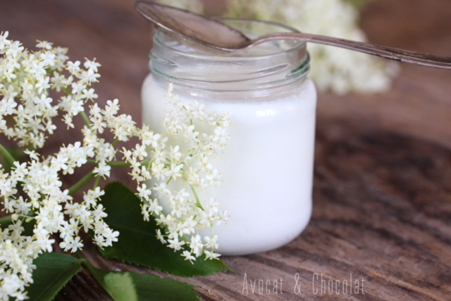 """alt=""""yaourt blanc à la fleur de sureau sur une planche en bois décoré de fleur de sureau"""""""