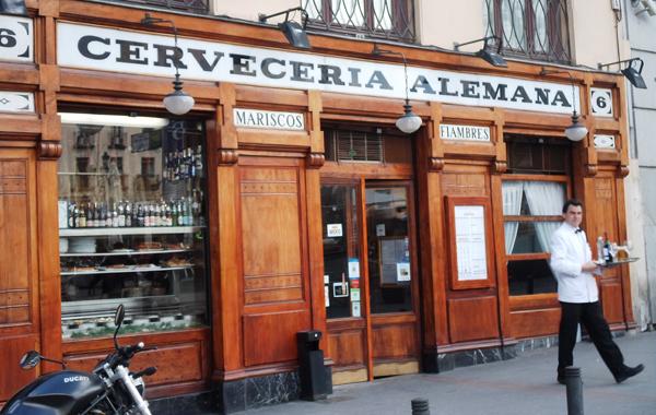Un camarero con chaquetilla blanca se dirige a la terraza, frente a la clasica fachada de madera de la cervecería.