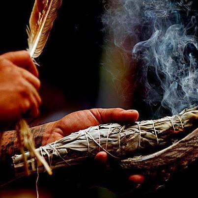 mano izquierda sosteniendo manojo de salvia desprendiendo humo, mano derecha sosteniendo pluma de animal