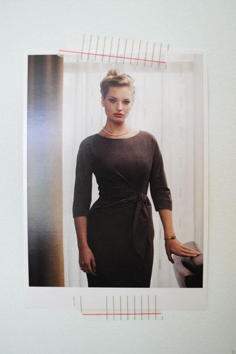 Vrouw in grijze jurk die recht de camera in kijkt.