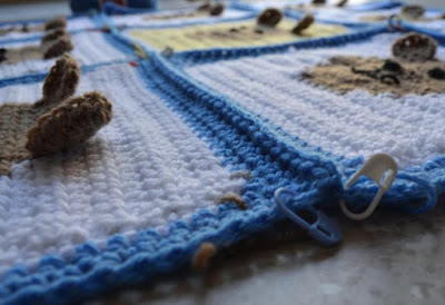 A close-up side view of the blanket with all the squares joined together. The seams are noticeable blue ridges of double crochet stitches. A blue stitch marker and a white stitch marker are attached to the edge of the blanket and can be seen in the foreground. The tan teddy bear ears can be seen raised above the surfact of the blanket..