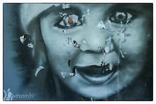 Szürke árnyalatos arc piros szemmel graffiti festmény Szegeden
