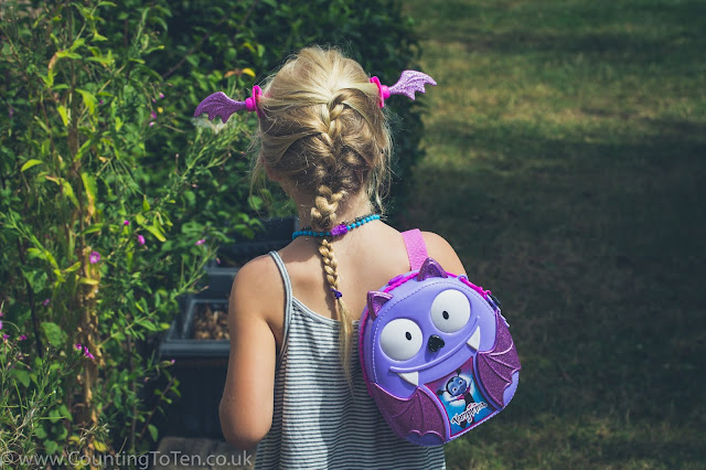 A rear view of the a young girl wearing the Bootastic Backpack and accessories from the set