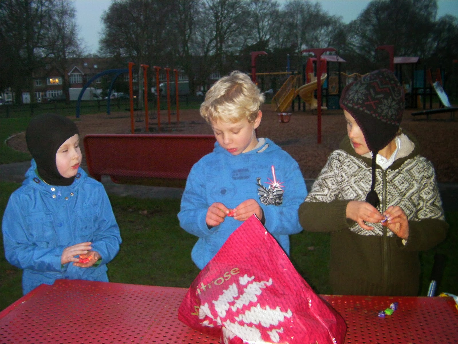 winter clothes at dusk sharing out starburst sweets
