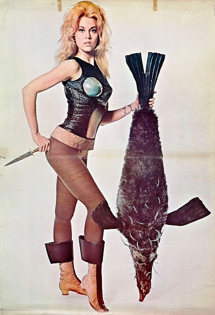 Jane Fonda as Barbarella posing while holding a dead animal
