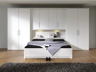 Vaste lit-pont blanc dans une chambre aux couleurs chaudes.