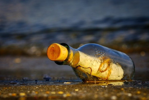 Na beira do mar, garrafa com uma mensagem dele. #PraCegoVer