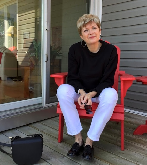 woman wearing white jeans, black sweatshirt and black loafers sitting in a red deck chair