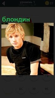 В помещении сидит парень блондин в одежде черного цвета