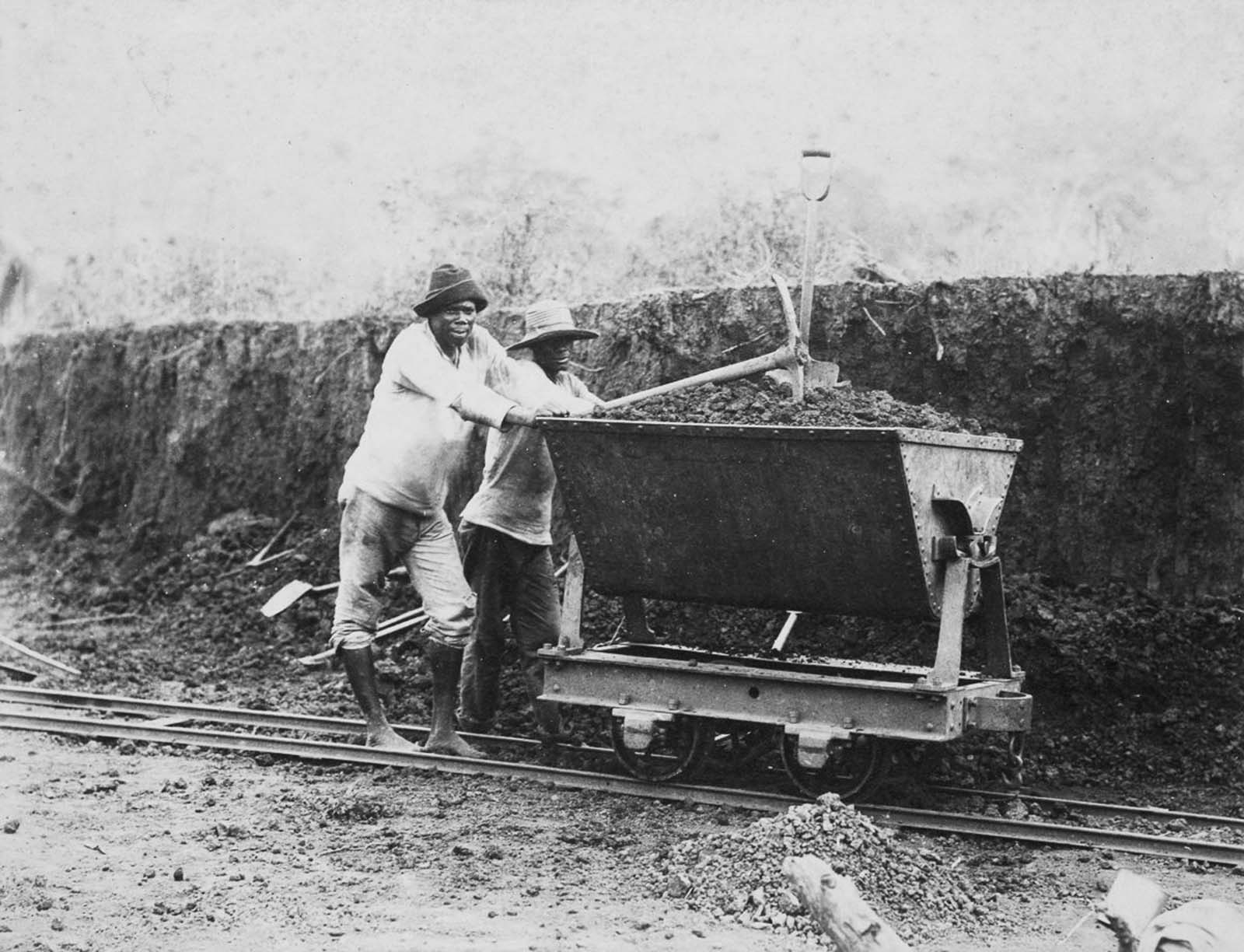 Jamaican laborers push a wagon of earth along a narrow-gauge railroad. 1885.