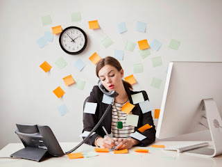 Busy girl with post notes at desk with computer and phone