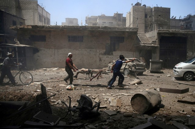 Men transport a casualty at a site hit by airstrikes in the rebel held Douma neighbourhood of Damascus, Syria
