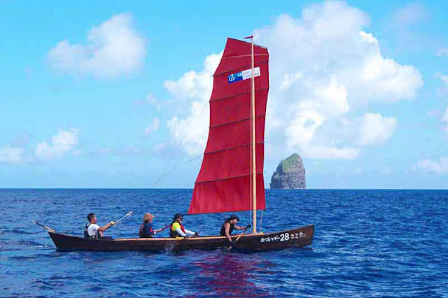 A sabani boat sailing and being paddled to Okinawa island