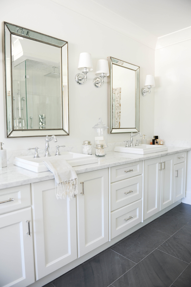 White bathroom with marble counter-tops.
