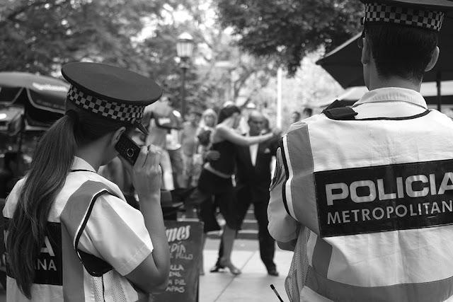 Alcuni poliziotti guardano una coppia che balla tango