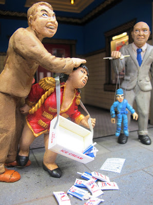 Three figures in front of a modern dolls' house miniature cinema lobby. One man is attacking an usherette, who is twisting his groin with her hand, the other is holding a marionette.