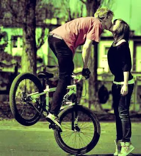 boy kissing girl in bicycle Cute kiss