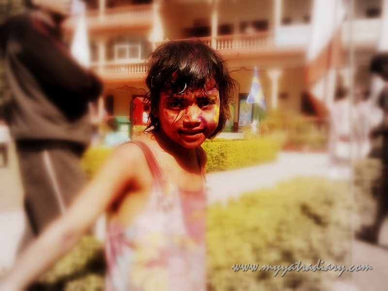 A child drenched in the colors of Holi