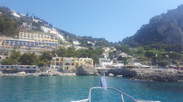 The nose of a boat edges into the harbour of Capri, with the clear blue sea meeting the rocky coast line. Pastel-coloured rows of houses line the hilly island.