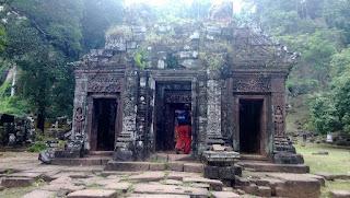 Храм Ват-Пху, как и остальные кхмерские храмы, ориентирован на восток. Основную ориентацию определяет священная гора и река. В 1400 метрах от храма располагается источник, 100 метров выше по холму. В км к востоку, на другой стороне реки Меконг, располагается город. Дороги от храма ведут к другим храмам, и в конечном итоге к храмовому комплексу Ангкор.  Вокруг храма расположены дворцы, известные как северный и южный, или мужской и женский, дворцы и храм расположены по одной оси. Назначение дворцов не ясно. Северный дворец лучше сохранился. В целом сооружения соответствуют ранне-ангкорскому стилю.   Кришна убивающий Камса на южной стене святилища Многие сооружения комплекса находятся в очень плохом состоянии.  К югу от святилища находится рельеф индуистской троицы, а к северу — отпечаток следа Будды, также изображения в форме слона и крокодила. Некоторые считают, что крокодилий камень связан с человеческими жертвоприношениями, описанными в китайских текстах VI века.