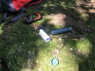 Ein Geocache und ein GPS Gerät liegen auf einem Stein