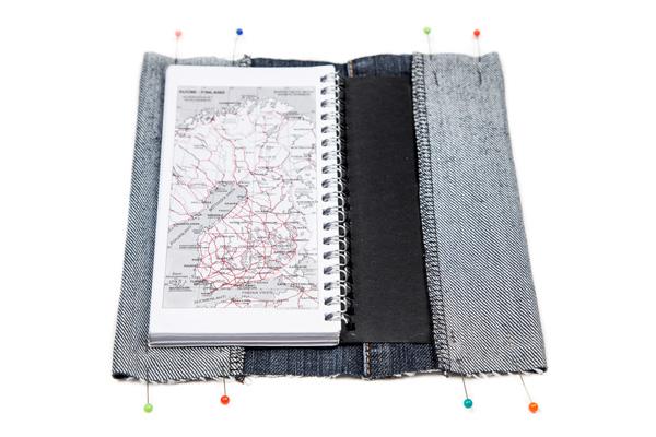Kalenterin farkkukansien taskujen taitto ja nuppineulakiinnitys