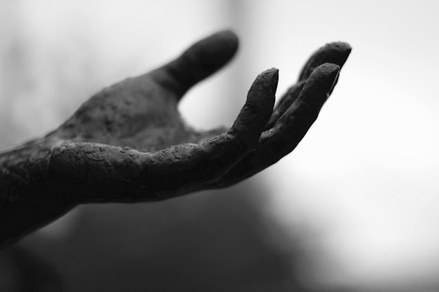 Statue or hand caked in mud. Monochrome.