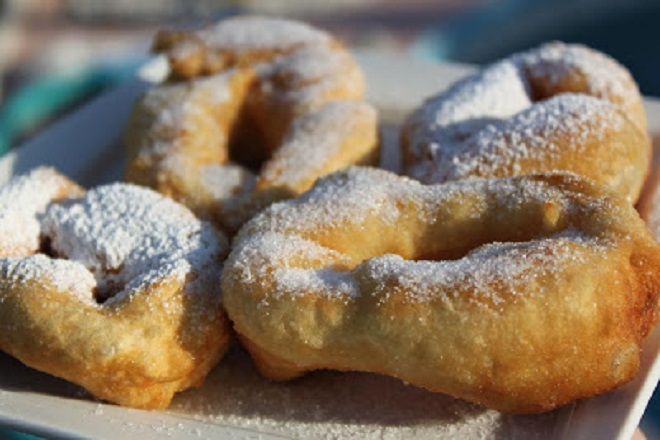 this is Zeppole  an Italian Fried bread dough fried in oil and sprinkled with sugar or powdered sugar found at most Catholic feasts and carnivals