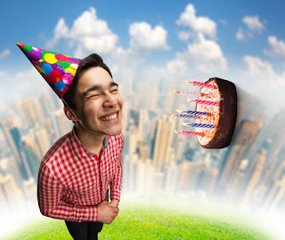 Photo of a Smiling Man in a Birthday Hat With a Cake and Candles