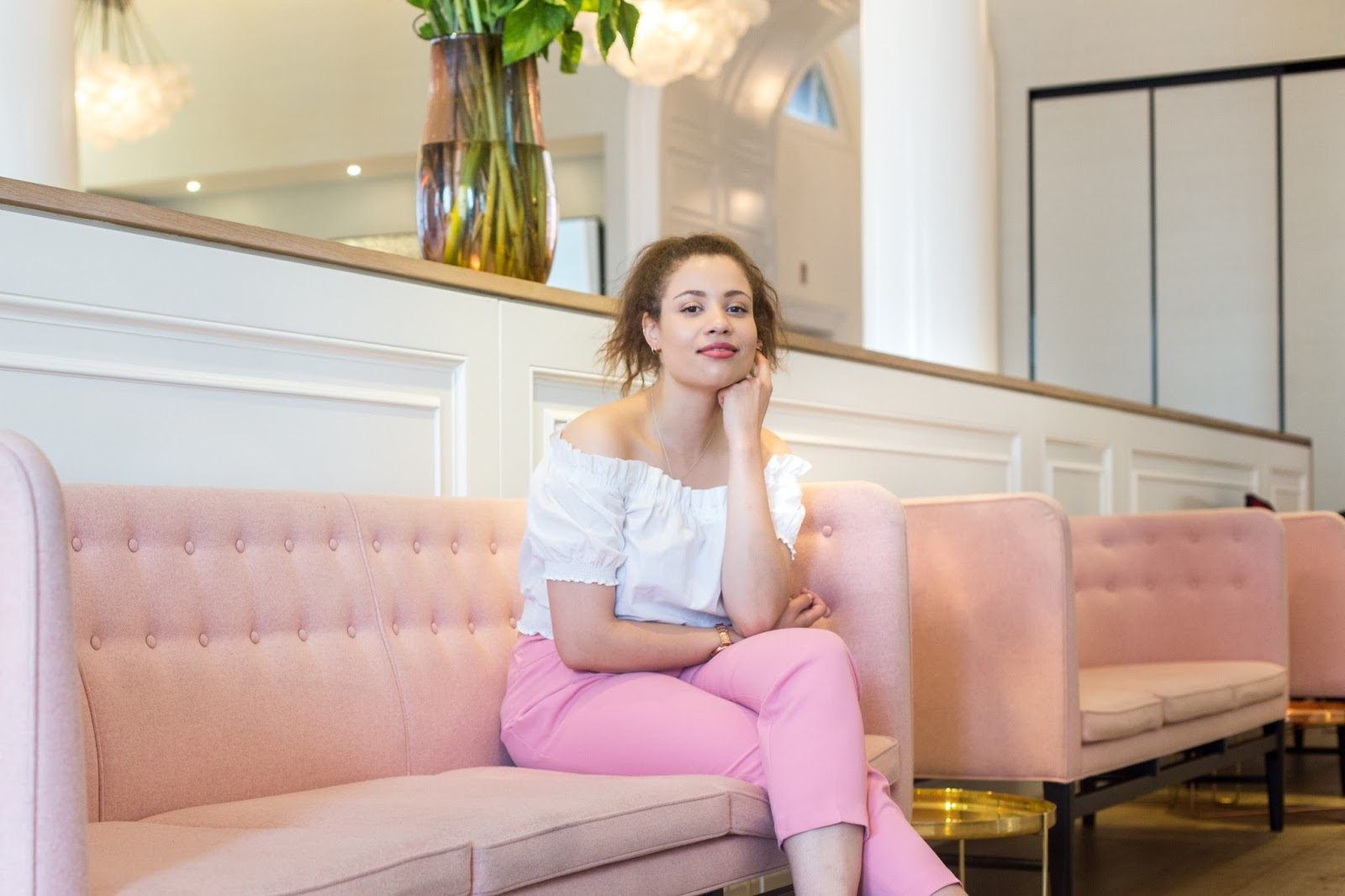An image of Eboni wearing pink Primark trousers and a white ruffle H&M top sitting on a sofa at Spring Somerset House