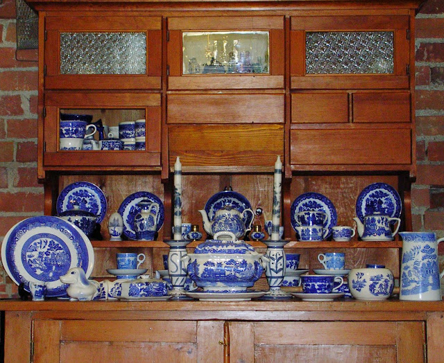 A large old kitchen hutch (c. late 1800s) filled with an assortment of old Blue Willow dinnerware.