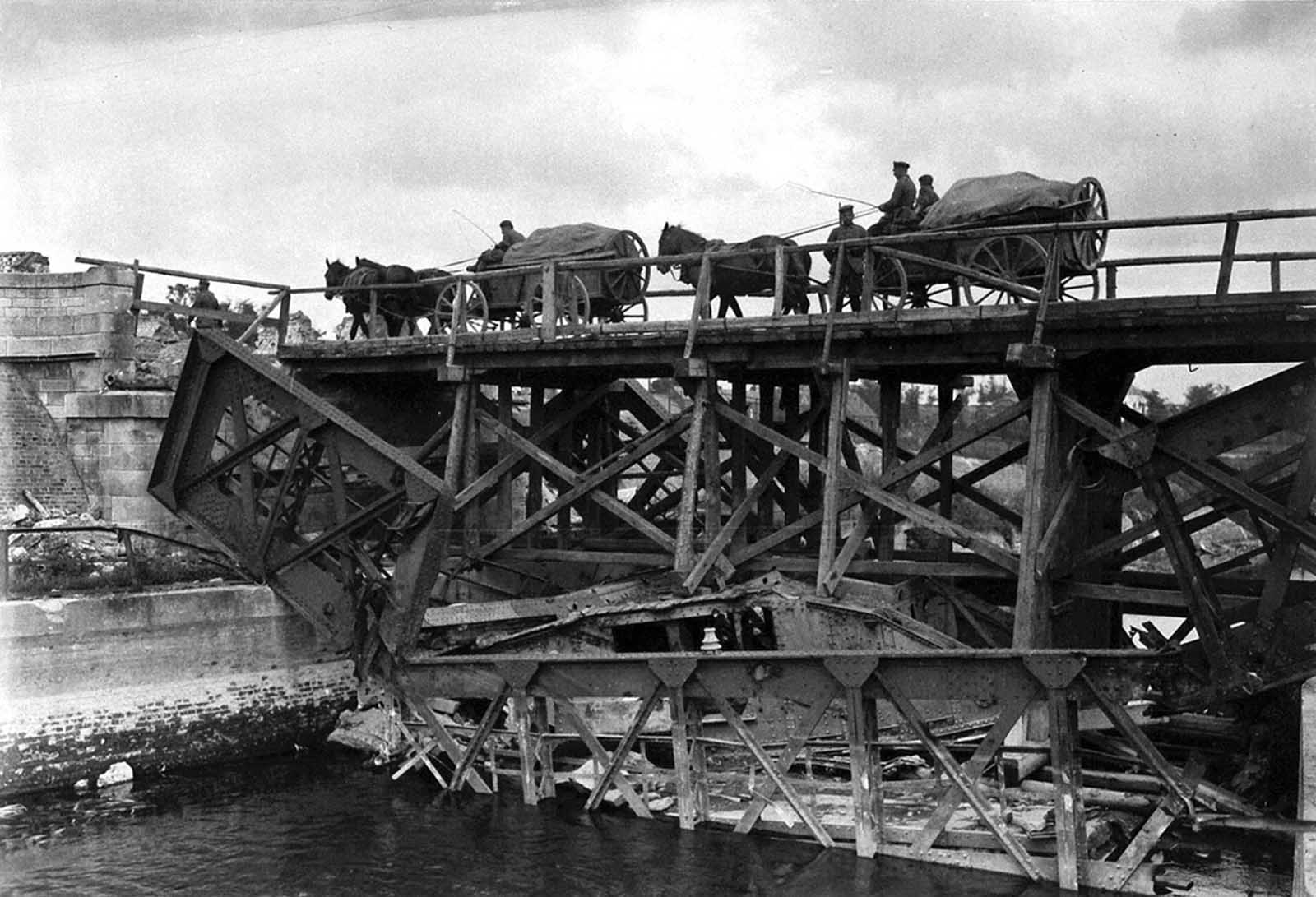 On the site where a steel bridge was destroyed, a wooden temporary bridge has been built in place. Note that an English tank which fell in the river when the former bridge was demolished now serves as part of the foundation for the new bridge over the Scheldt at Masnieres.