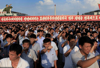 North Koreans stage mass rally as thousands raise their fists in show of strength after Donald Trump threatens to destroy the regime