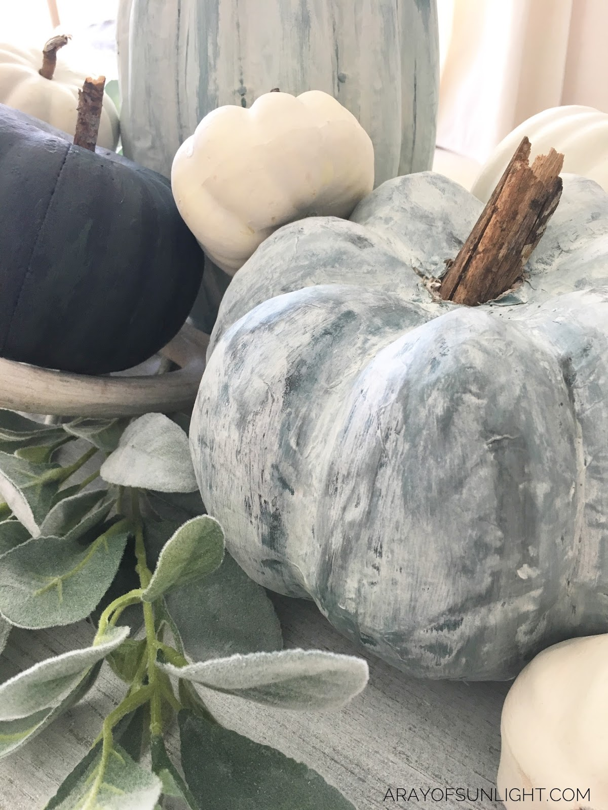 Learn how to make these painted fall pumpkins... the perfect project to get your fall decor going. We used Country Chic Paint to make these muted blue and green pumpkins and mixed them with lambs ear and antlers to go with our farmhouse decor. By A Ray of Sunlight