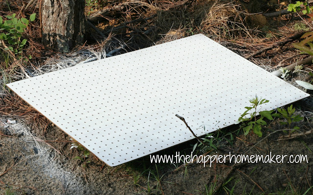 A white pegboard laying on the ground
