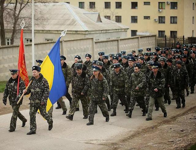 Soldados ucranianos desarmados marcham contra tropa russa que dispara por cima de suas cabeças