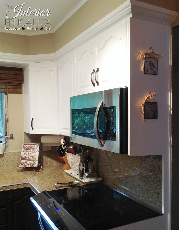 Helpful tips for painting golden oak kitchen cabinets white for a lasting finish plus a two-toned look for a budget-friendly kitchen makeover.