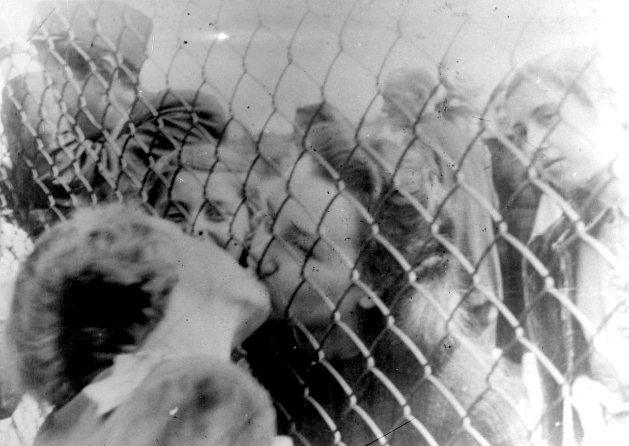 дві єврейки, імовірно родички, цілуються на прощання через загорожу у Лодзинському ґетто, 1940-і