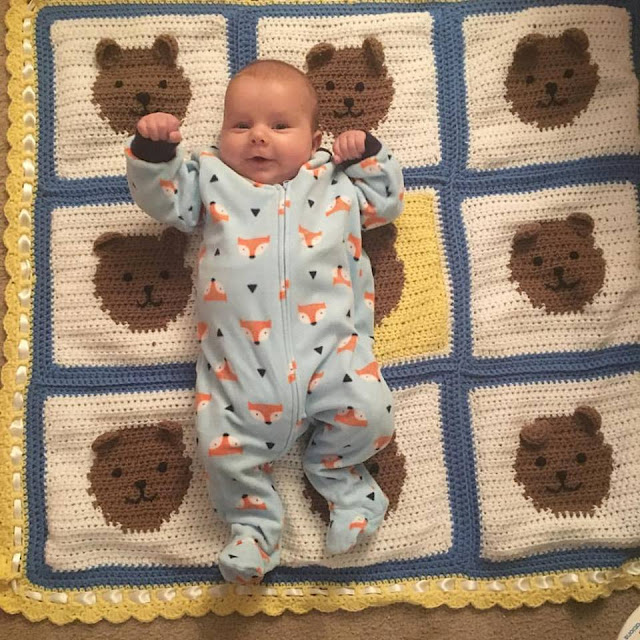 Top and partial view of teddy bear blanket with baby laying on top on his back, looking at the camera and smiling. Baby is wearing a cotton zip-up long-sleeved jumpsuit in light blue with a pattern of white and orange fox faces and black triangles on it. Description of blanket can be found in previous photo.