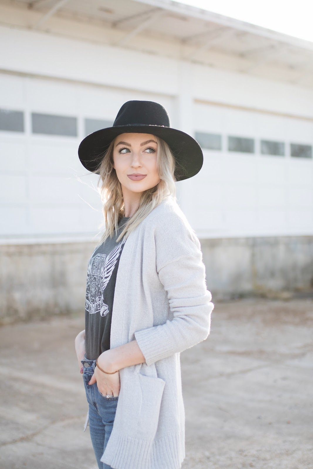 gray cardigan with a graphic tee, jeans, and hat
