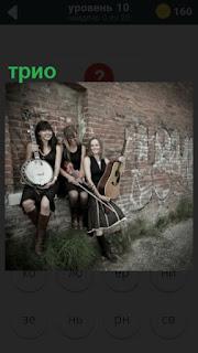 трио девушек с инструментами около стены играют