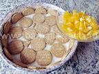 Tort de portocale preparare reteta - asezam un strat de biscuiti si peste punem bucatelele de portocala