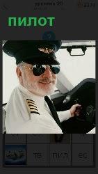 мужчина в форме пилота за штурвалом стоит