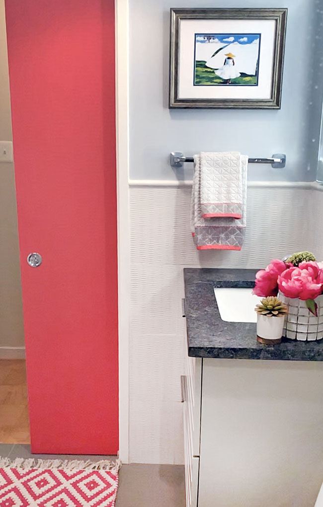 Fuchsia pocket door in white and gray bath